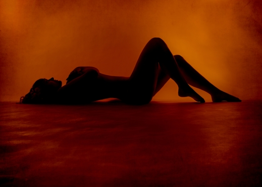 Naked sexy woman silhouette lying at orange background